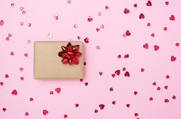 Caixa de presente com um laço vermelho na lateral em um fundo rosa. espaço livre para texto. férias, natal, dia dos namorados.