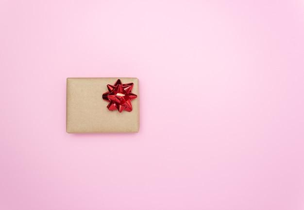 Caixa de presente com um laço vermelho na lateral rosa