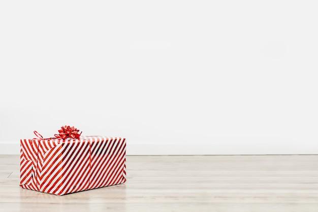 Caixa de presente com um laço vermelho sobre um piso de madeira contra uma parede branca. o conceito de parabéns pelos feriados aos entes queridos, entrega de presentes para os feriados.