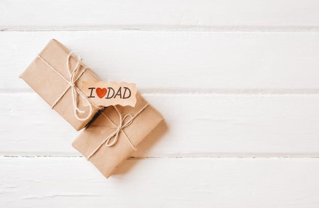 Caixa de presente com uma etiqueta no espaço em branco de madeira. dia dos pais ou conceito de aniversário.