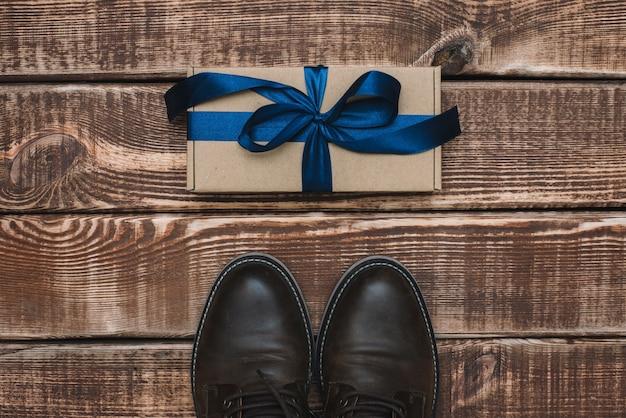 Caixa de presente com uma fita azul e sapatos de couro masculino em uma mesa de madeira. dia dos pais. presente para um homem. postura plana.