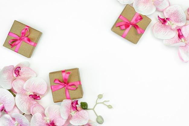 Caixa de presente com uma fita rosa e flores da orquídea