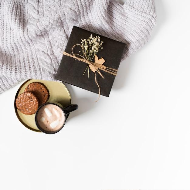 Caixa de presente com uma xícara de café e biscoitos na mesa