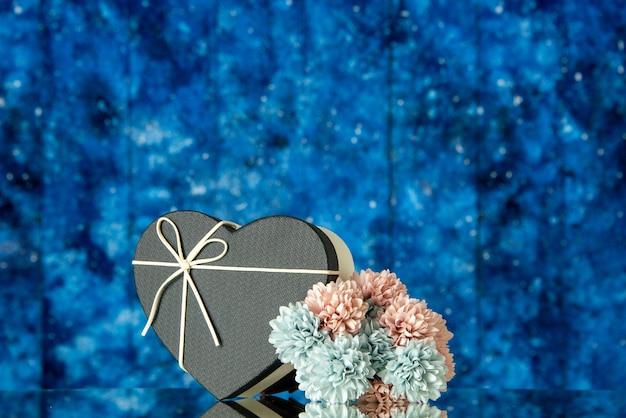 Caixa de presente com vista frontal em forma de coração e flores coloridas de capa preta em fundo azul desfocado