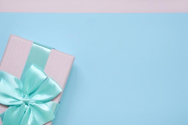 Caixa de presente cor-de-rosa com uma curva azul em um fundo azul acima da vista superior. lugar para o texto. conceito de férias, aniversário, presente.