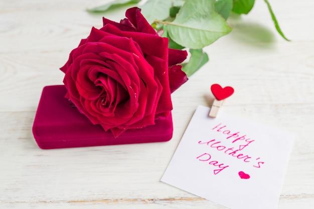 Caixa de presente da joia e rosa vermelha do bautiful no fundo de madeira. cartão para dia das mães
