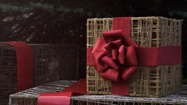 Caixa de presente de armação de arame dourado embrulhada com fita vermelha sob a árvore de natal