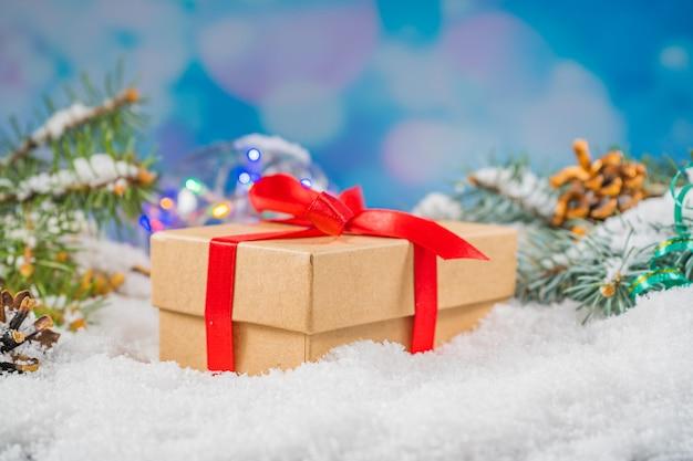 Caixa de presente de artesanato decorativo com laço vermelho na neve fresca contra um bokeh de fundo de natal