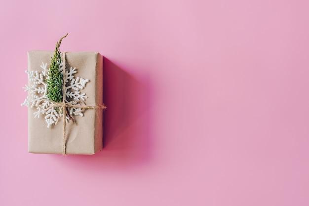 Caixa de presente de brown no fundo cor-de-rosa. cartão de férias com estilo minimalista