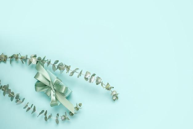 Caixa de presente de cor verde natural com laço de cetim e raminhos de eucalipto na cor menta. composição elegante primavera monocromático com espaço de cópia.