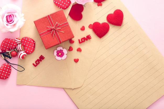 Caixa de presente de dia dos namorados com corações vermelhos e rosas no envelope de carta