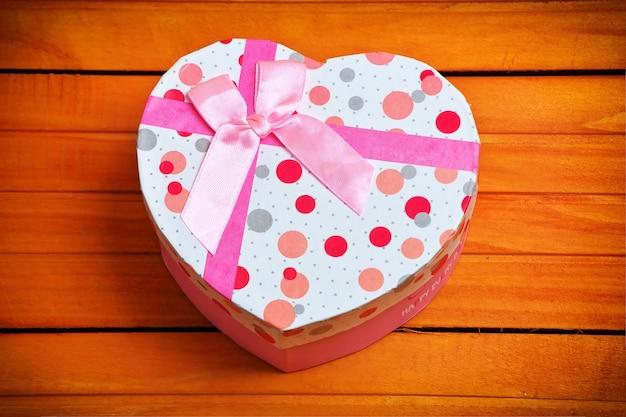 Caixa de presente de dia dos namorados com fundo de madeira em forma de coração. fundo de férias.
