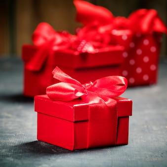 Caixa de presente de dia dos namorados presentes com laço vermelho no fundo de madeira