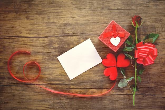 Caixa de presente de dia dos namorados vermelha no cartão de madeira flor rosa e fita de caixa de presente arco - envelope amor correio valentine letter