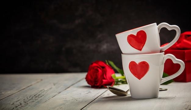 Caixa de presente de dia dos namorados xícaras e rosas em um fundo de madeira