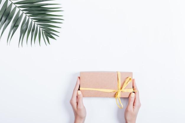 Caixa de presente de feriado com uma fita nas mãos das mulheres e a folha de palmeira na superfície branca