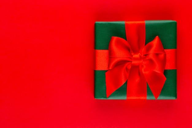 Caixa de presente de feriado de natal em fundo vermelho.