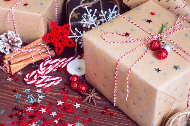 Caixa de presente de feriado de natal na mesa festiva de neve decorada com pinhas