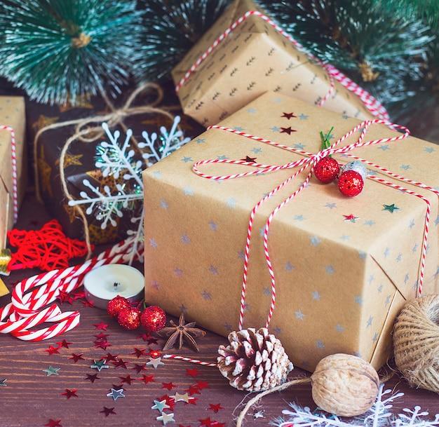 Caixa de presente de feriado de natal na mesa festiva de neve decorada com ramos de pinheiro