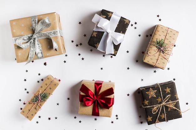 Caixa de presente de feriado de natal na mesa festiva decorada com estrelas de brilho