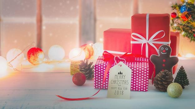 Caixa de presente de feriados de natal e ano novo com ornamento decorativo na mesa de madeira branca com efeito de neve caindo. natal de milho e feliz ano novo 2018 tag de papel.gifts e parabéns.