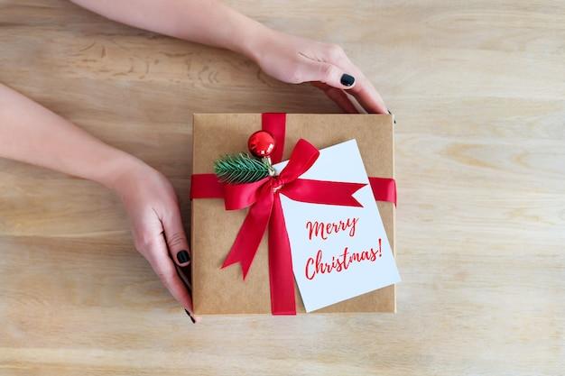 Caixa de presente de férias flatlay presente nas mãos da mulher em um fundo de madeira para férias de inverno, natal ou ano novo