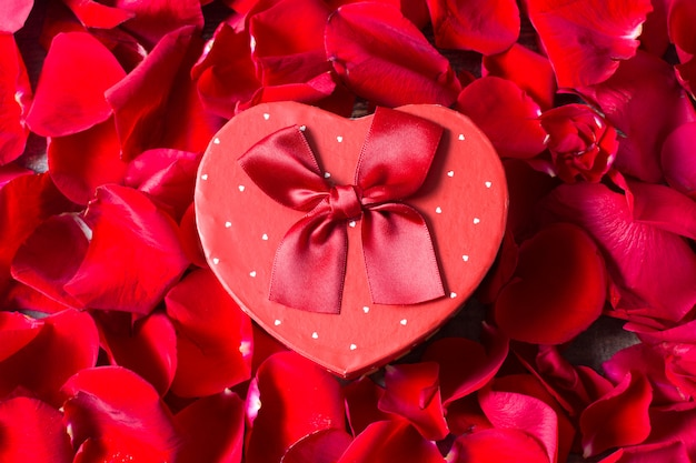 Caixa de presente de forma de coração com fundo de pétalas