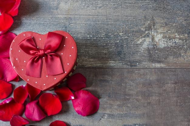 Caixa de presente de forma de coração com pétalas no espaço da cópia da mesa de madeira