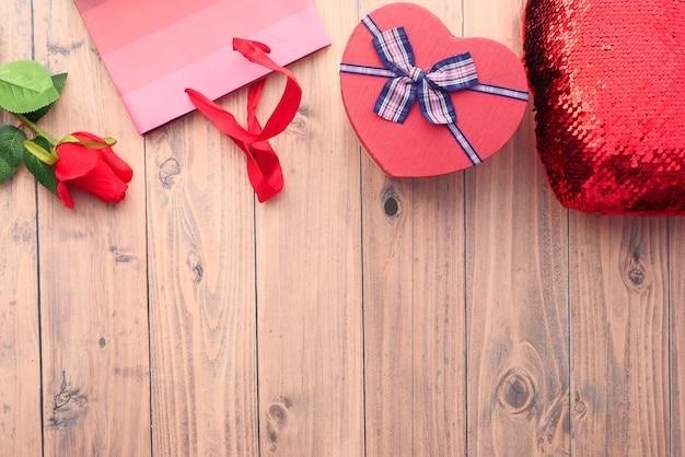 Caixa de presente de forma de coração, sacola de compras e flor rosa na mesa