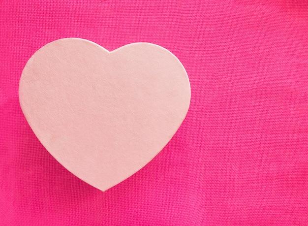 Caixa de presente de forma de coração sobre rosa
