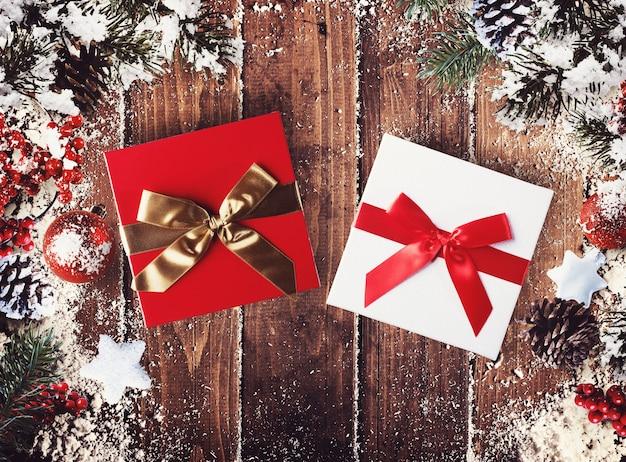 Caixa de presente de natal apresentada no meio de decorações de natal em pranchas de madeira