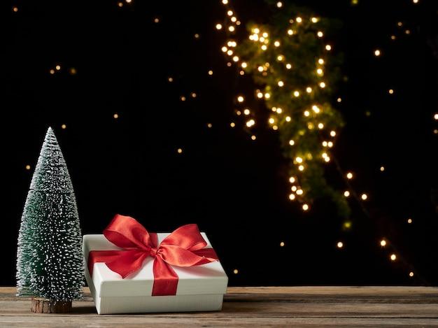 Caixa de presente de natal com abeto na mesa de madeira contra um fundo escuro, espaço para texto