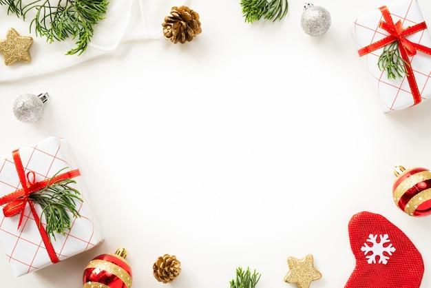 Caixa de presente de natal com cones de bola e pinho vermelhos sobre fundo branco.