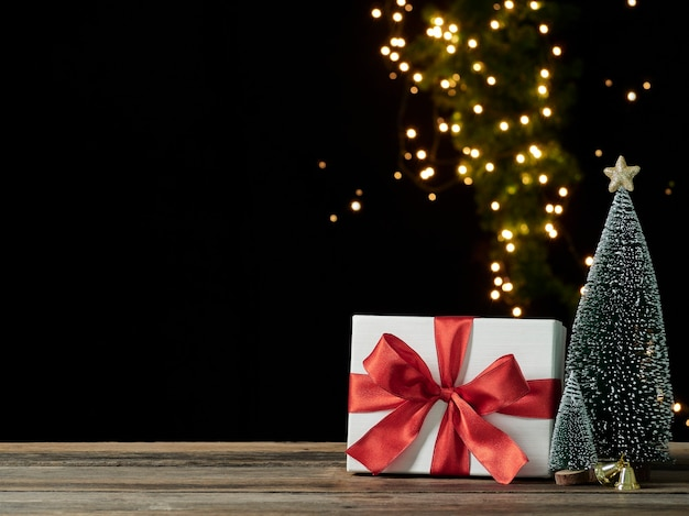Caixa de presente de natal com enfeites em mesa de madeira contra luzes festivas borradas em fundo escuro, espaço para texto