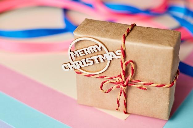 Caixa de presente de natal com fita de inscrição feliz natal em plano de fundo multicolorido com fitas