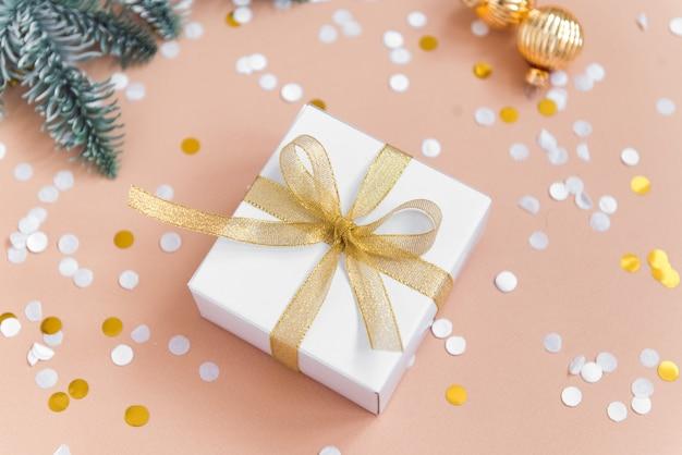 Caixa de presente de natal com fita dourada em fundo bege com bolas de confete e decoração