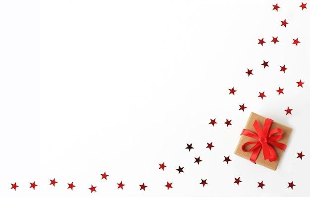 Caixa de presente de natal com fita vermelha com confetes de estrelas.