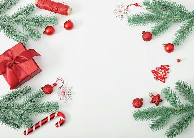 Caixa de presente de natal com galhos de pinheiro e brinquedos isolados
