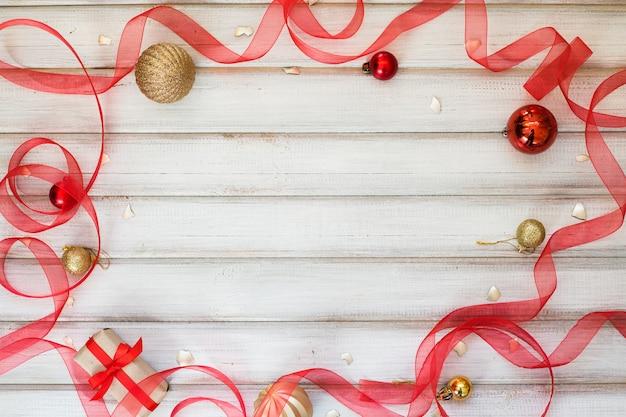 Caixa de presente de natal com laço de fita e bola de brinquedo em fundo branco de madeira
