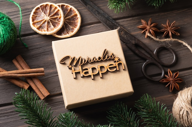 Caixa de presente de natal com letras de madeira milagres acontecem. idéias de embrulho de presentes. desenho natural. passo a passo