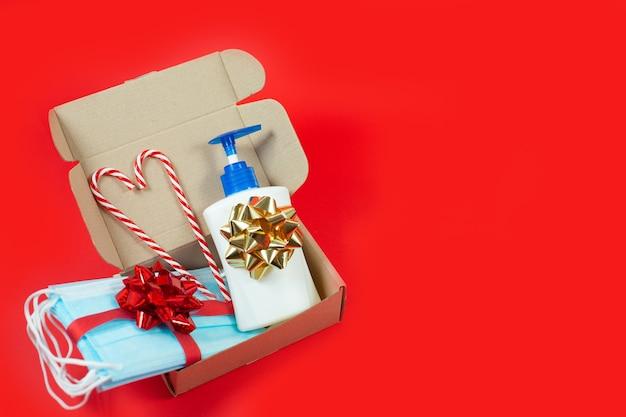 Caixa de presente de natal com máscaras descartáveis, desinfetante para as mãos e pirulito em fundo vermelho.