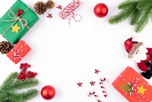 Caixa de presente de natal com ramos de abeto, pinhas, bagas vermelhas sobre fundo branco.