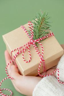 Caixa de presente de natal com um galho de árvore de natal em mãos humanas