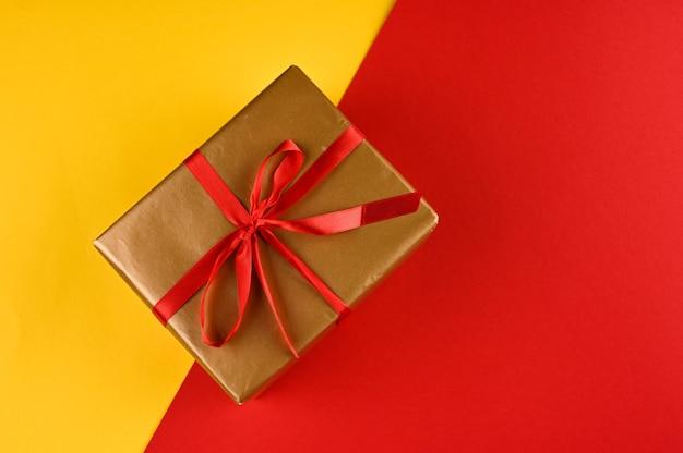 Caixa de presente de natal contra um fundo amarelo-vermelho. cartão de férias.