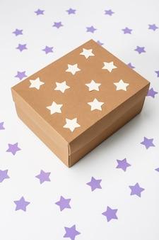 Caixa de presente de natal de madeira sobre a parede branca com estrelas