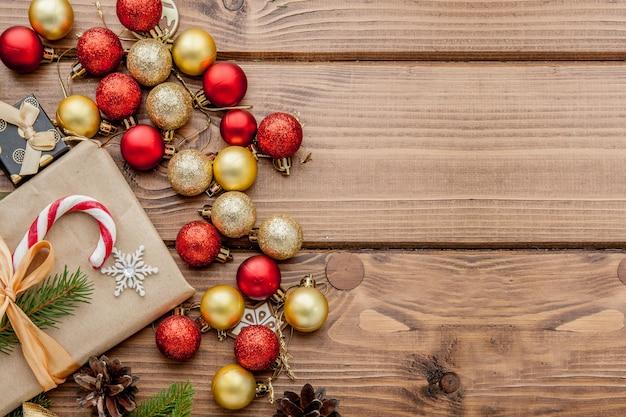 Caixa de presente de natal, decoração de alimentos e galho de árvore do abeto na mesa de madeira. vista superior com copyspace