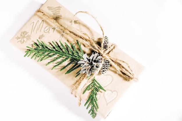 Caixa de presente de natal decorada com pinhas e galhos em fundo branco. presentes de natal e ano novo. feito à mão.