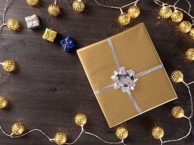 Caixa de presente de natal dourada com luzes de natal douradas em fundo de madeira. pequenos presentes.