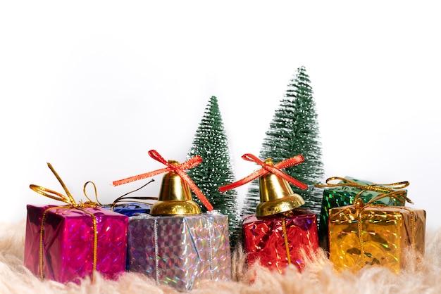 Caixa de presente de natal e árvore com sinos de ouro, pinhas, bola vermelha e branca