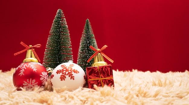 Caixa de presente de natal e árvore com sinos de ouro, pinhas em fundo vermelho